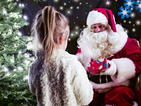 Santa at Dobbies handing present to child