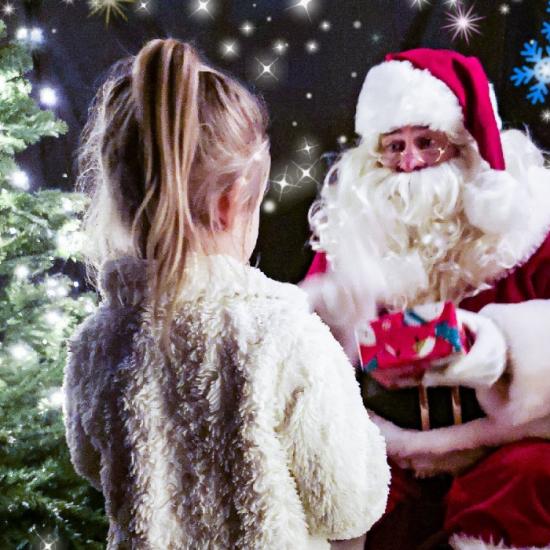 Santa at Dobbies handing present to child