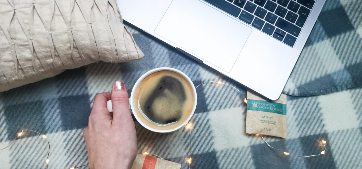flatlay image of hand holding coffee cup, a laptop and 2 sachets of london nootropics