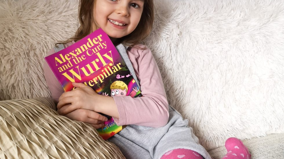 Eva holding the book, Alexander and the Curly Wurly Caterpillar
